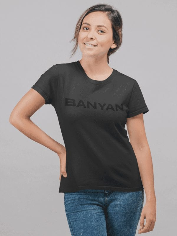 Young Woman Standing Wearing Banyan Black on Black T-Shirt