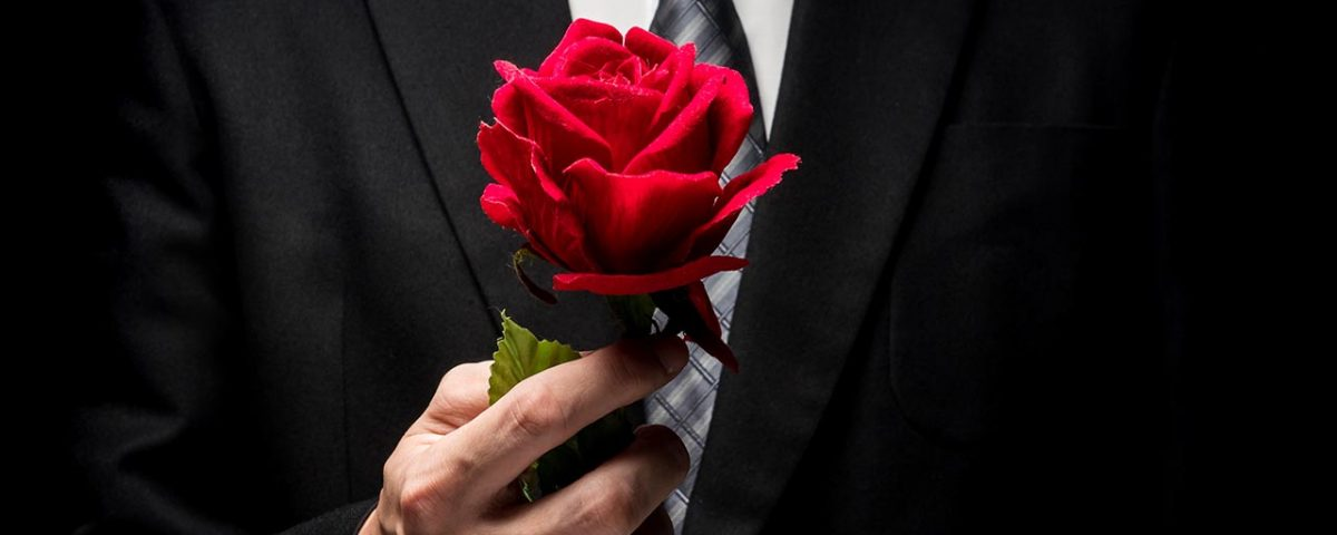 man in tux holding rose